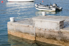 Inflatable boat with motor. Inflatable boat with outboard motor in Adriatic sea with concrete pier in foreground Stock Photo