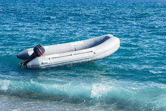 Inflatable boat with a motor swings on sea waves near the shore Royalty Free Stock Photos