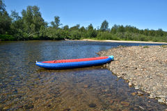 Inflatable boat on the pebbly Bank of the river. Stock Photos