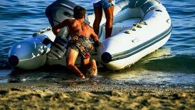 Inflatable boat on the seashore, sandy beach. stock photos