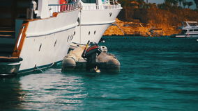 Inflatable boat tied to pleasure boats in the Red Sea near the beach. Slow Motion stock video