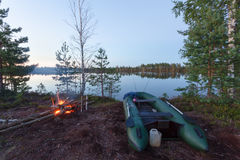 The inflatable boat  with two spinning on the lake at sunrise and bonfire Royalty Free Stock Photos