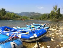 Inflatable boats with oars rafts for rafting along a mountain. River in front of a beautiful scenery Royalty Free Stock Photography