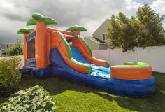 Inflatable bounce house water slide in the backyard. Outdoor Inflatable bounce house water slide at an sitting in a backyard ready for a birthday party Royalty Free Stock Photos