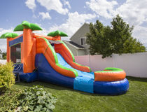 Inflatable bounce house water slide in the backyard. Outdoor Inflatable bounce house water slide at an sitting in a backyard ready for a birthday party Stock Photos