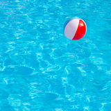 Inflatable colorful ball floating in swimming pool Stock Photos