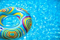 Inflatable colorful Rubber Ring floating in blue Royalty Free Stock Images