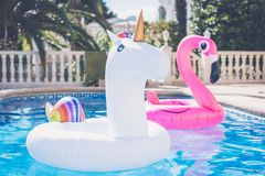 Free Inflatable Colorful White Unicorn And Pink Flamingo At The Swim Pool. Vacation Time In The Swimming Pool With Plastic Stock Images - 118063414