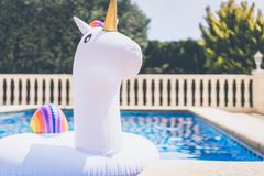 Inflatable colorful white unicorn at the swim pool. Holidays week in the swimming pool with plastic toys. Relaxation and Royalty Free Stock Photos