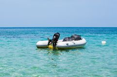 Inflatable dinghy boat with outboard motor moored in tropical sea royalty free stock photos