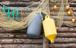 Inflatable fenders and netting. Hanging on a wooden wall Stock Photos