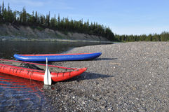 Inflatable kayaks on the shore taiga rivers. Royalty Free Stock Photography