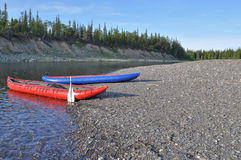 Inflatable kayaks on the shore taiga rivers. Stock Photos