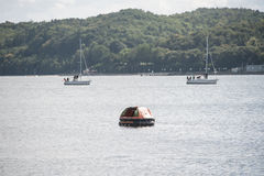 Inflatable lifeboat in waters. Inflatable lifeboat next to sailboats in water off shores Royalty Free Stock Image
