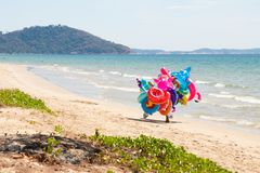 Inflatable lifebuoys seller walks along a snow-white beach with blue water royalty free stock photo