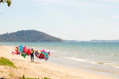 Inflatable lifebuoys seller walks along a snow-white beach with blue water stock photography
