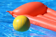 Inflatable mattress and ball in pool Stock Photo