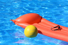 Inflatable mattress and volleyball in pool. Inflatable mattress and ball swimming in the pool by the sun Royalty Free Stock Image