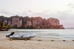 Inflatable motor boat with oars. On a sandy beach against the backdrop of mountains and the sea.  stock photography