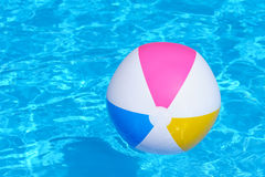 Inflatable multy colored plastic ball in swimming pool. An inflatable multy colored plastic ball in a shiny blue swimming pool Royalty Free Stock Photo