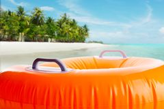 Inflatable orange cushion on the beach Royalty Free Stock Photography