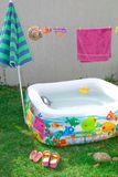Inflatable pool in the garden, with an umbrella. royalty free stock photos