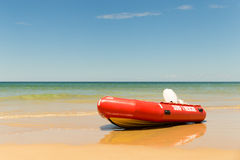 Inflatable Rescue Boat Life Saving. An inflatable rescue boat (IRB) sits on a beach under a clear sunny sky with calm surf in the background stock photos