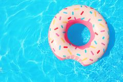 Inflatable ring floating in swimming pool on sunny day. Top view with space for text royalty free stock photography