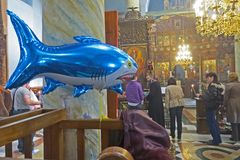 Inflatable shark in the orthodox church. Balloon for children with helium amongst praying people. Stock Images