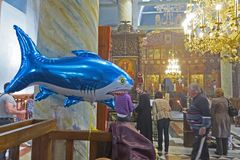 Inflatable shark in the orthodox church. Balloon for children with helium amongst praying people. Stock Photos