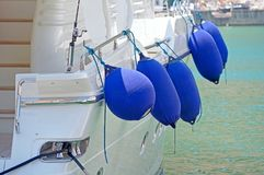 Inflatable ship fenders hanging. Small ship fenders hanging above pleasure yacht hull royalty free stock photos