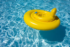 Inflatable Swimming Pool Float Tube Ring Baby Seat. Yellow inflatable for kid or child with seat floating on clear blue swimming pool water Royalty Free Stock Image