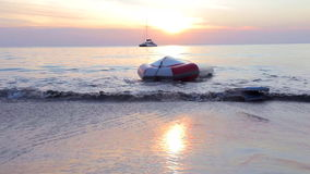Inflatable upturned boat near the beach. Sea wave beating inflatable upturned boat. Lonely ship and bright sunset in the distance stock video