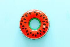 Inflatable watermelon ring over blue wooden background.  stock photo