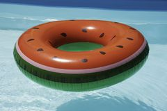 Inflatable watermelon ring in pool on sunny day stock images