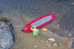 Inflatable whitewater stand up paddleboard from above. Senior male paddler with inflatable whitewater stand up paddleboard on a shore of mountain river - Poudre royalty free stock images