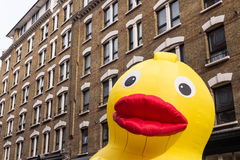 Inflatable yellow duck face standing in front of houses Stock Photos