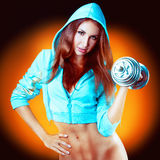 Inflated girl with dumbbells in a sports jacket Royalty Free Stock Photos