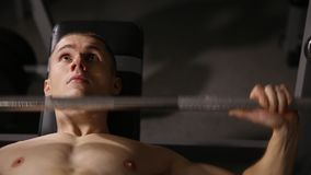 Inflated strong man with big muscles raises the bar lying on the bench close up. Inflated strong man with big muscles raises the bar lying on the bench close up stock footage