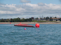 Inflatible oil boom  towards Tauranga beach. Royalty Free Stock Photo