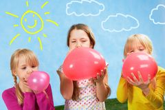 Inflating. Photo of three cute girls inflating balloons Royalty Free Stock Image