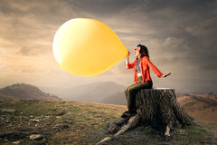 Inflating balloon. Young woman dressed as a clown inflating yellow balloon Stock Photography