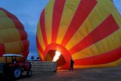 Inflating a hot air balloon. Inflating a red and yellow hot-air balloon at dawn Royalty Free Stock Photography