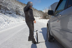 Inflating the tire of a Car. Man repairs bike in forest, winter. Bicyclist pumping air into the wheel. Man uses a bicycle pump. Pumping air into an empty wheel Stock Images