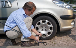 Inflating tyre. Kneeling man, inflating the right front tyre of his car at a gas station Royalty Free Stock Photos