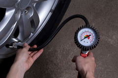 Inflating the wheels. Inflating the automobile wheels via a pump Stock Photo