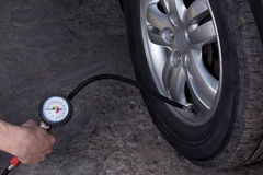 Inflating the wheels. Inflating the automobile wheels via a pump Stock Images