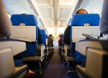 Inflight cabin. Passengers inside the cabin of a commercial airliner during flight Royalty Free Stock Image