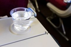 Inflight cabin glass of water on table. Drink to prevent dehydration. Whien flying royalty free stock photography
