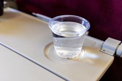 Inflight cabin glass of water on table. Drink to prevent dehydration. Whien flying stock image